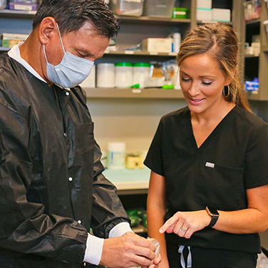Dr. Jimmy Gardiner and a dental assistant reviewing dental work